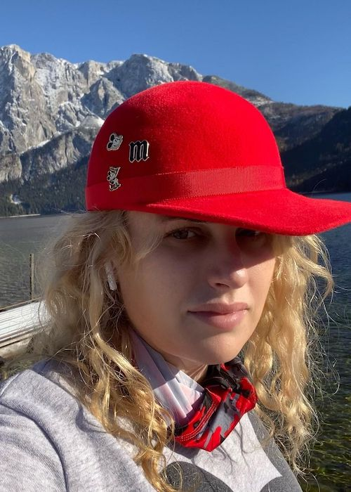 Rebel Wilson wearing red cap and showing pins in 2020