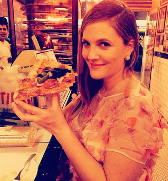 Drew Barrymore eating a slice of pizza