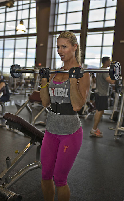 Callie Bundy working out her biceps with barbell rod.