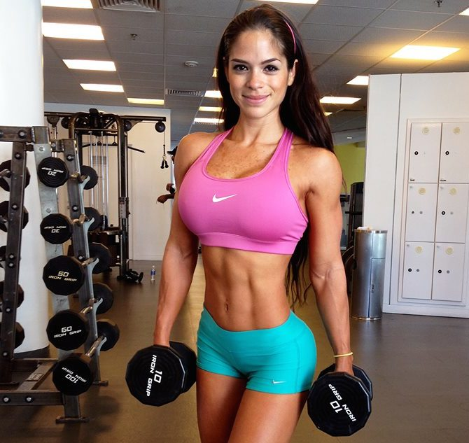 Michelle Lewin working out in the  gym with dumbbells.