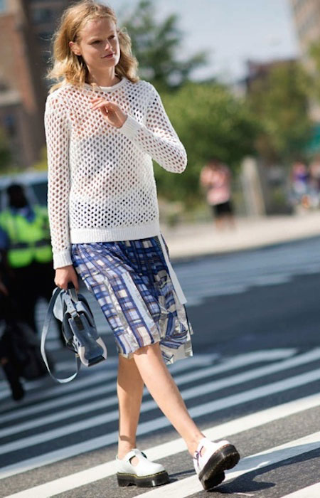 Hanne Gaby Odiele pairs a Sacai blue plaid skirt with a white perforated sweater, and finishes with white Dr. Martens T Bar shoes.