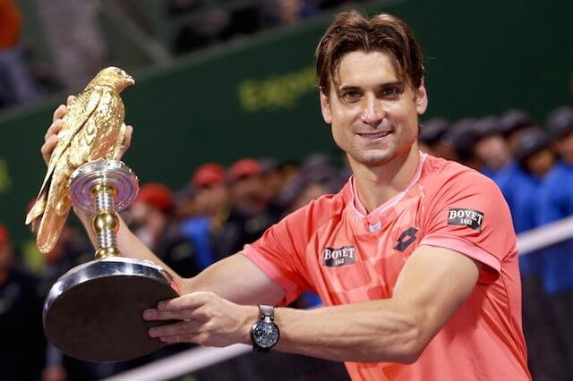 David Ferrer poses with the trophy after beating Czech player Tomas Berdych in the final of the Qatar Open at the Khalifa Tennis Complex in Doha in 2015