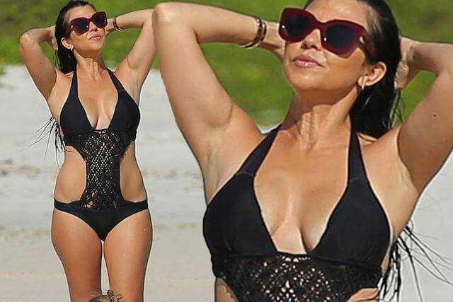 Kourtney Kardashian flaunts smokin' figure in cut-out black swimsuit as she soaks up