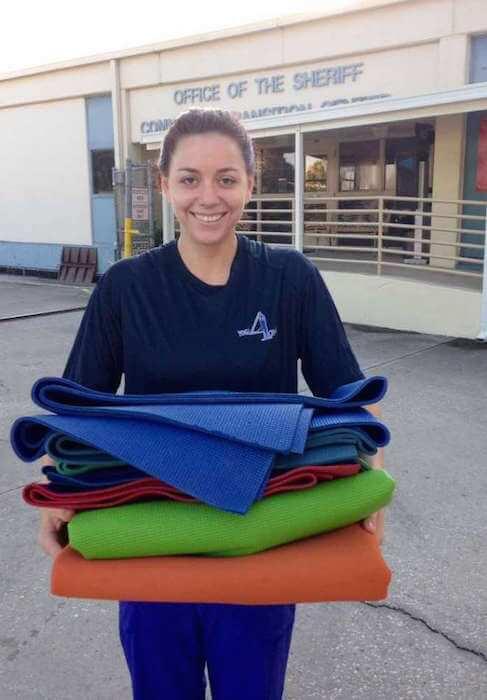 Kathryn Thomas holding yoga mats