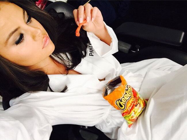 Selena Gomez with cheetos... Oops, she won't be having them for some time now