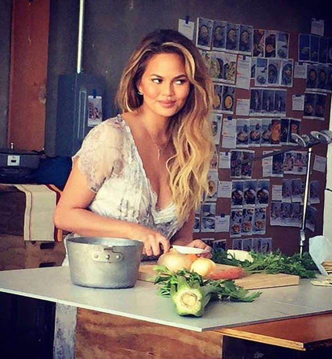 Chrissy Teigen in the kitchen cutting veggies