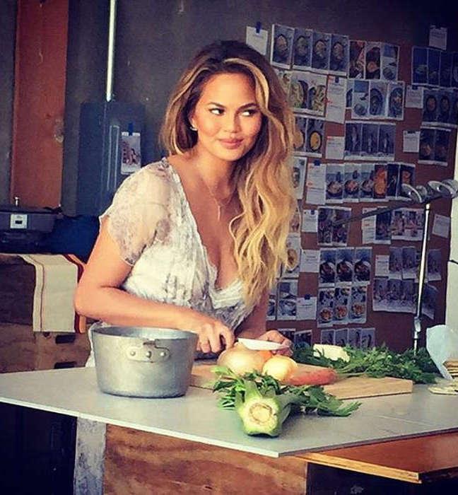 Chrissy Teigen in the kitchen cutting veggies