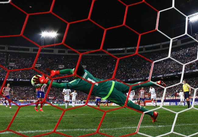 Keylor Navas defending the penalty shot by Atlético Madrid player Antoine Griezmann during a match between Real Madrid CF and Atletico Mardid on October 4, 2015 in Madrid, Spain