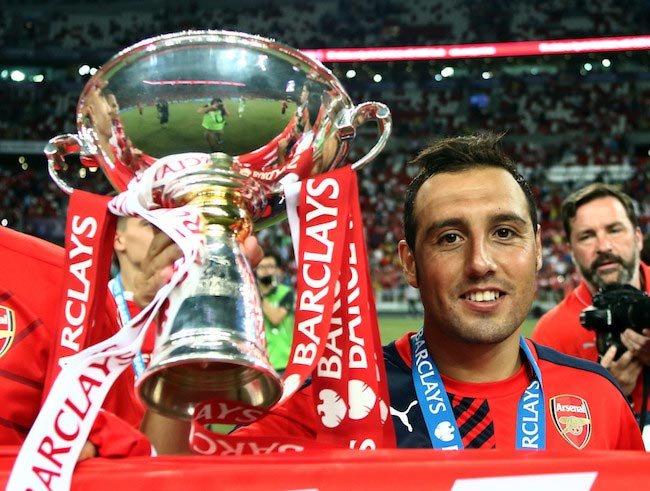 Santi Cazorla celebrates while holding the Barclays Asia Trophy after a win against Everton on July 18, 2015 in Singapore