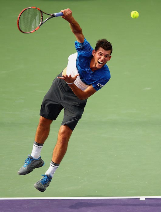 Dominic Thiem serves against Novak Djokovic in a Miami Open at Crandon Park Center on March 29, 2016