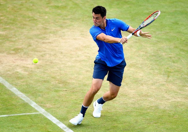 Bernard Tomic trying to return the ball with a backhand shot in a match of the Aegon Tournament against Gilles Muller on June 17, 2016