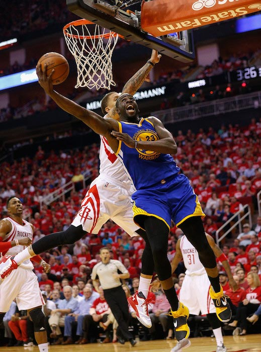 Draymond Green tries to score over Michael Beasley of Houston Rockets during a match on April 21, 2016