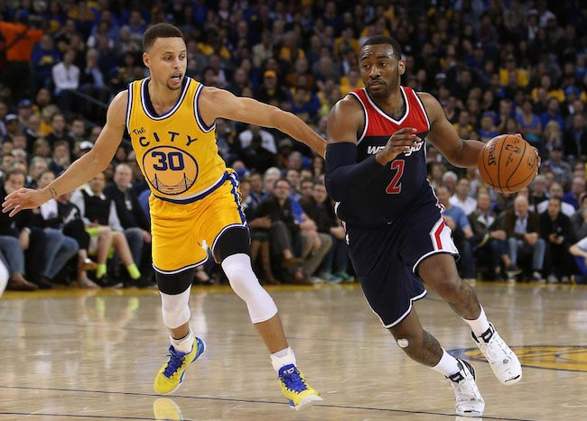 John Wall in action against Stephen Curry on March 29, 2016 in Oakland, California