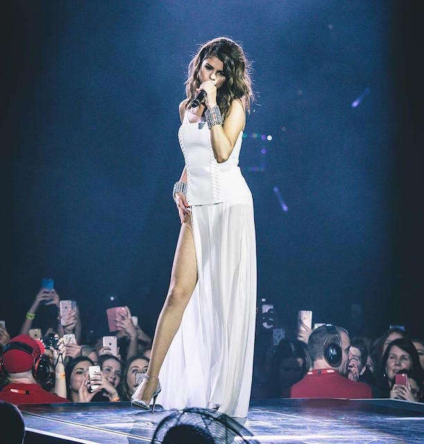 Selena Gomez in white corset dress wearing silver cuffs during Revival Tour in August 2016
