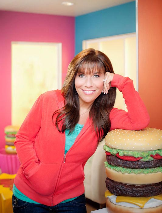 Lisa Lillien leaning on a burger prop