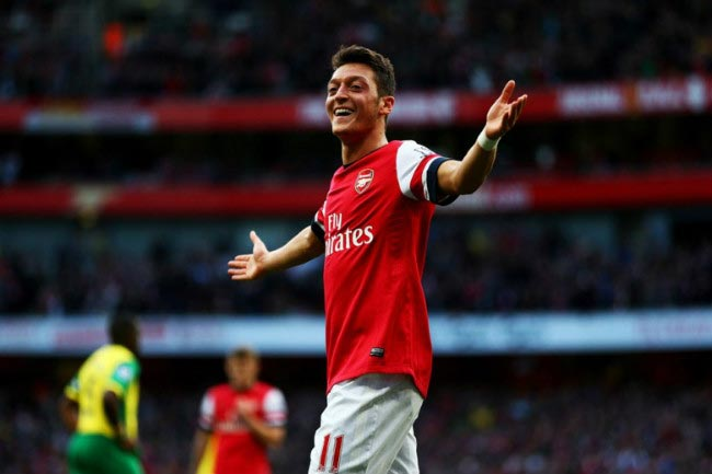 Mesut Özil celebrates after scoring a goal in thumping 4-1 home victory against Norwich in 2013