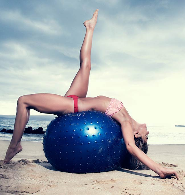 Anna Kaiser on beach exercising on a ball