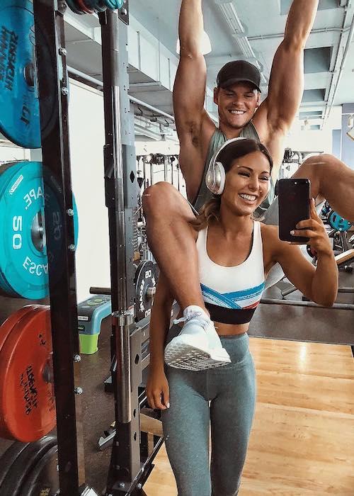 Louise Thompson in a mirror selfie with boyfriend Ryan Libbey in the gym in June 2018