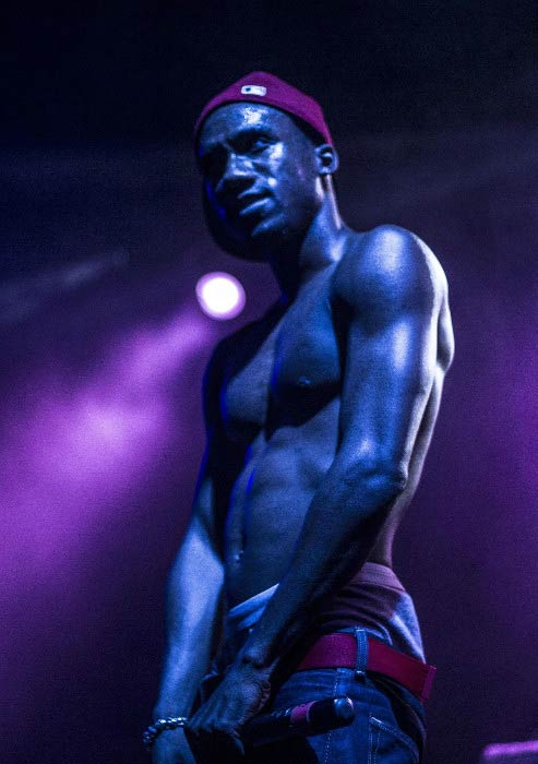 Hopsin shirtless performing on stage at his concert in 2015
