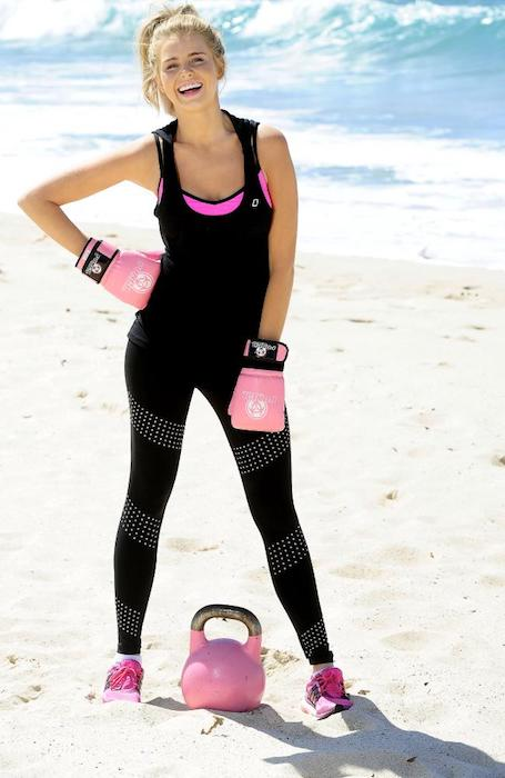 Tegan Martin in workout gear doing kettlebell workout seaside