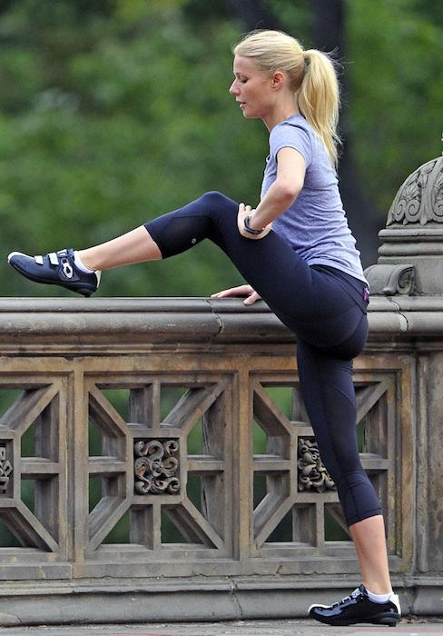 Gwyneth Paltrow stretching her legs while wearing yoga pants