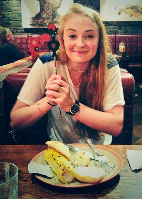 Sophie Turner posing before eating corn