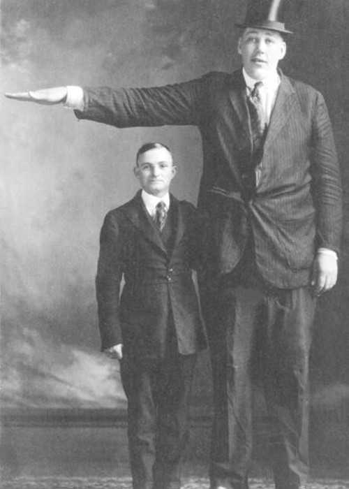A Photo of Actor John Aasen Standing Next to a Normal Sized Man