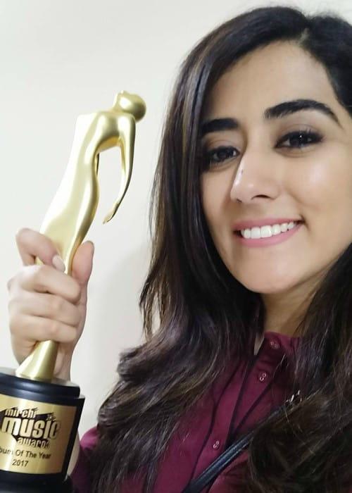 Jonita Gandhi showing her Mirchi Music Award in a selfie as seen in January 2018