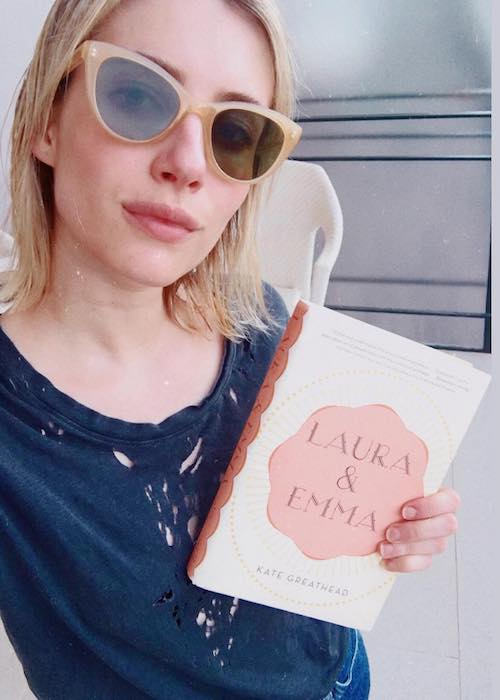Emma Roberts holding the book Laura and Emma by Kate Greathead in April 2018