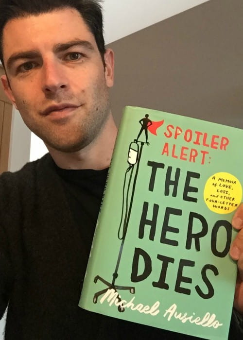 Max Greenfield holding the book The Hero Dies by Michael Ausiello in December 2017