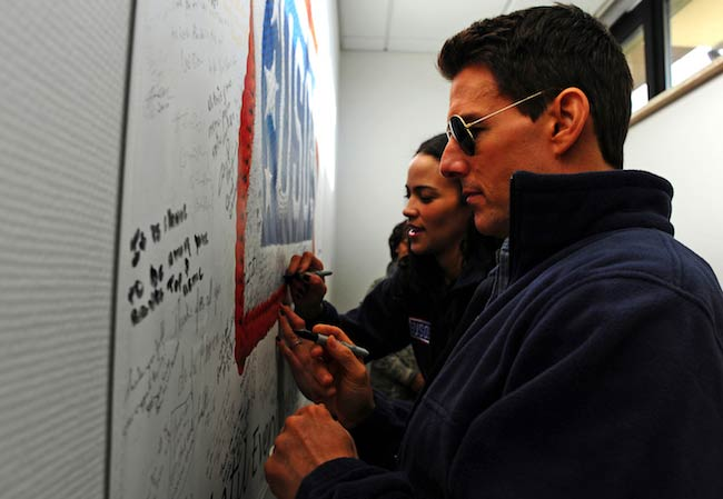 Tom-Cruise-and-Paula Patton signing a USO poster while on a Contingency Aeromedical Staging Facility tour in Germany in December 2011
