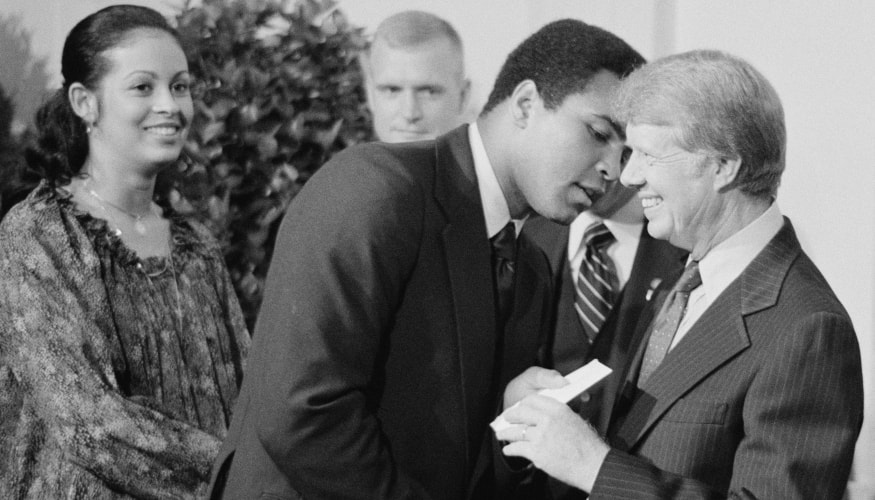 Muhammad Ali, accompanied by his wife Veronica Porsche Ali , exchanging greetings with President Jimmy Carter while attending a White House dinner celebrating the signing of the Panama Canal Treaty Washington, D.C.