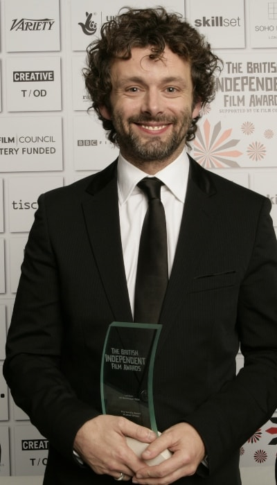 Michael Sheen posing with his BIFA Award