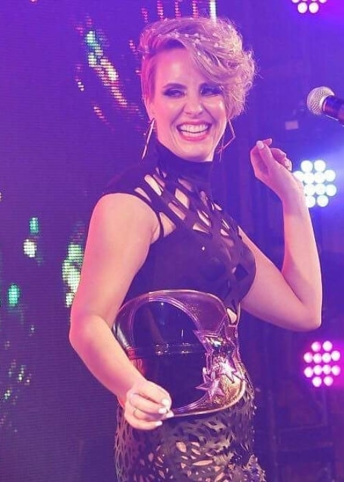 Claire Richards sporting a wide grin while on stage during an event