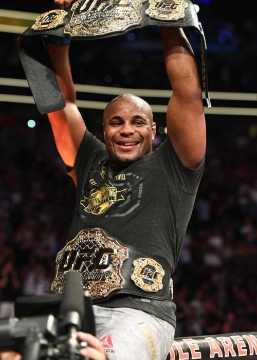 Daniel Cormier showing his belts in July 2018