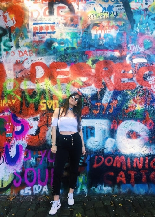 Emma Taylor posing in front of the John Lennon Wall in October 2017