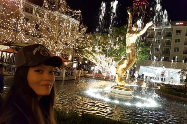 Hana Mae Lee in a selfie with a dazzling backdrop
