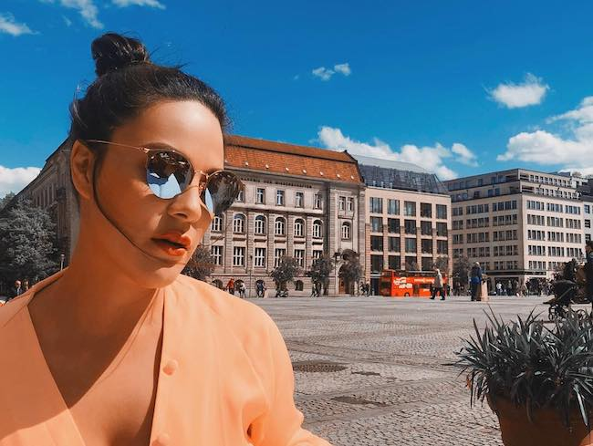 KC Concepción wearing Ray Ban sunglasses in the bright sun at Gendarmenmarkt Berlin in May 2018