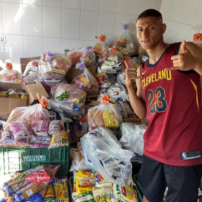Richarlison posing with food collected from the charity match in May 2018