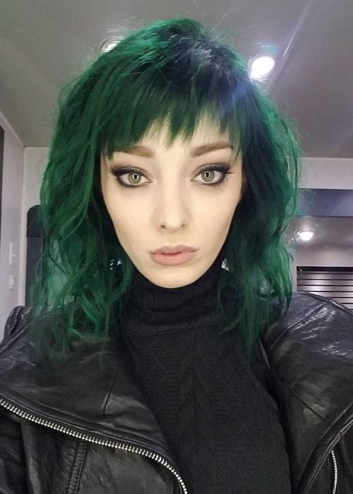 Emma Dumont sporting green hair in a selfie in July 2018