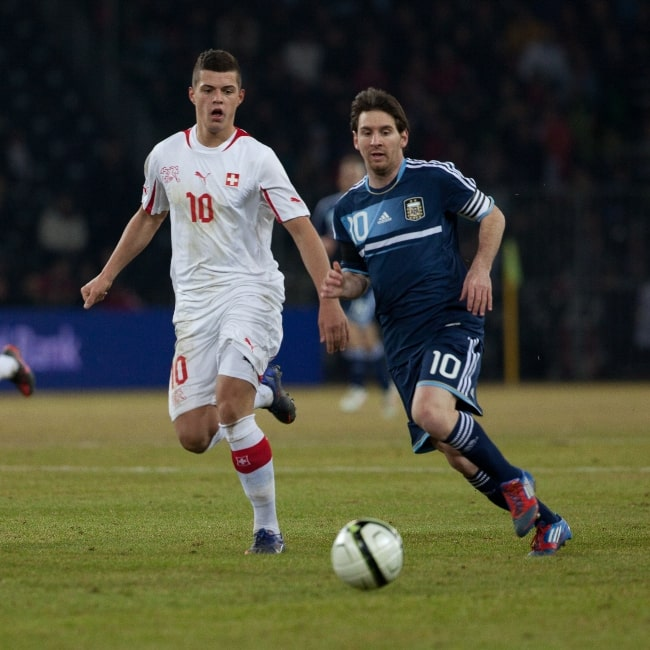 Granit Xhaka (Left) chasing the ball alongside Lionel Messi in a match in February 2012
