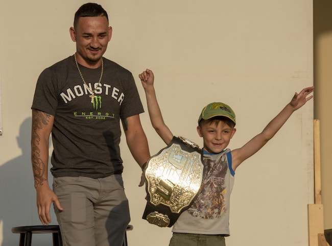 Max Holloway with a child from the audience holding his championship belt at the USO Spring Tour at Yokota Air Base Japan on April 22, 2018