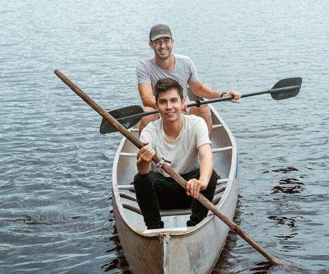 Sam Tsui canoeing with Joel Manduke behind him in August 2018