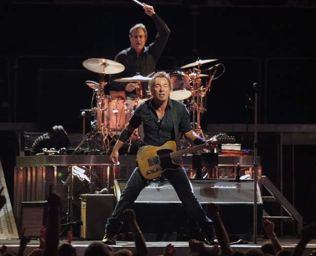Bruce Springsteen performing at a concert with Max Weinberg in the back in August 2008