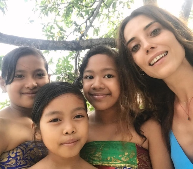 Cansu Dere in a selfie with some kids in Bali, Indonesia in June 2017