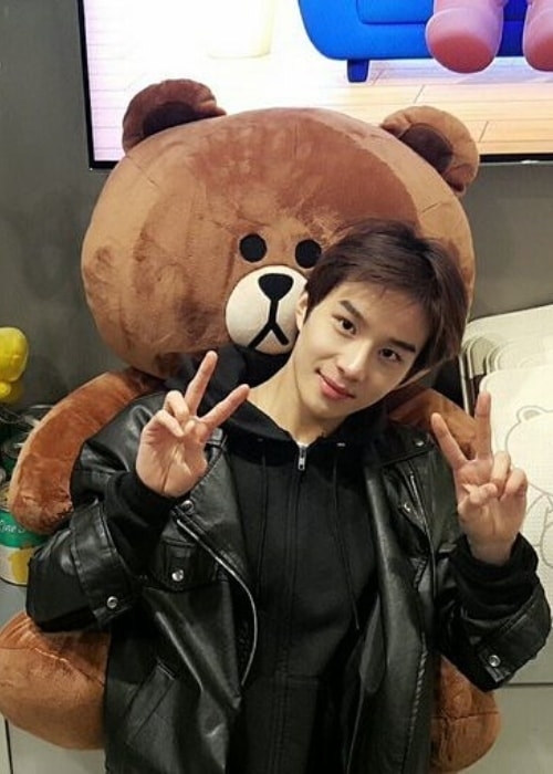 Jungwoo posing with a stuffed bear in May 2017