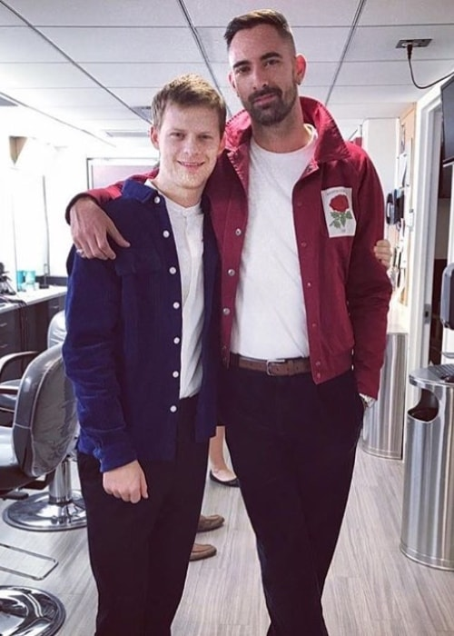 Lucas Hedges in a blue shirt and ginger hair while posing for the camera