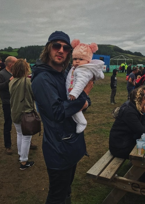 Gethin Davies posing with a baby at The Big Tribute Festival in August 2018