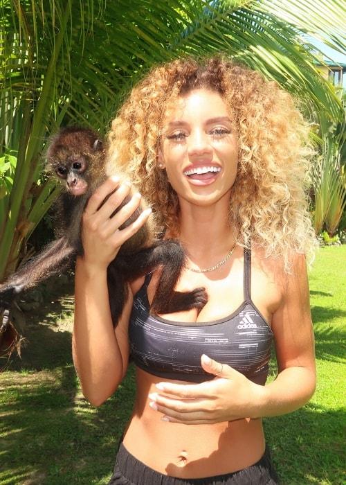 Jena Frumes posing with a Spider Monkey in Roatán, Islas De La Bahia, Honduras in August 2018