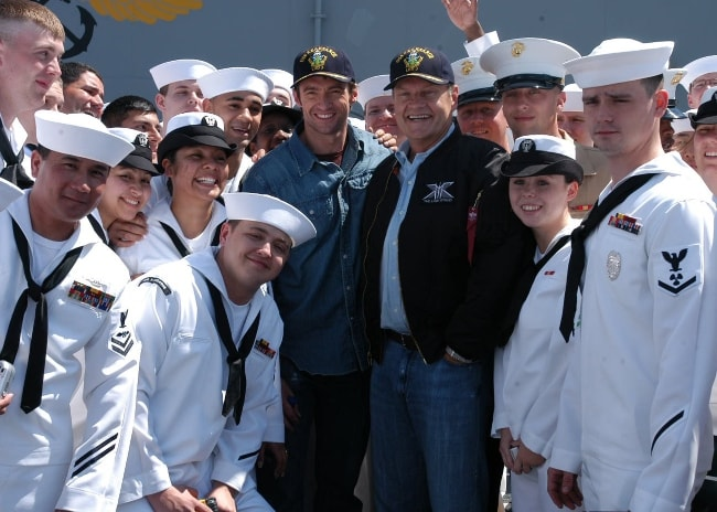 Kelsey Grammer (Center Right) and Hugh Jackman (Center Left) posing with crew members on the flight deck aboard the amphibious assault ship USS Kearsarge (LHD 3) in May 2006